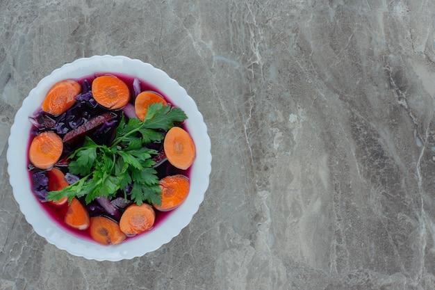 Gezonde mix van bieten, wortelschijfjes en peterselie garneer in een kom op marmer.