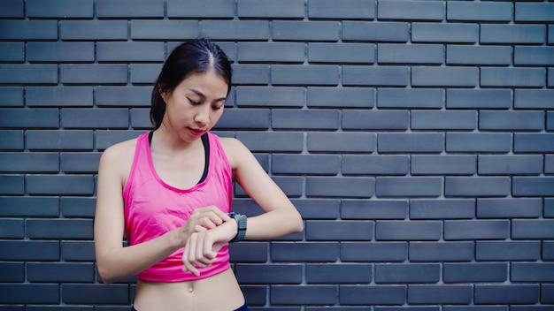 Gezonde mooie jonge aziatische atletenvrouw die en vooruitgang plaatsen die de monitor van het harttarief kijken kijken