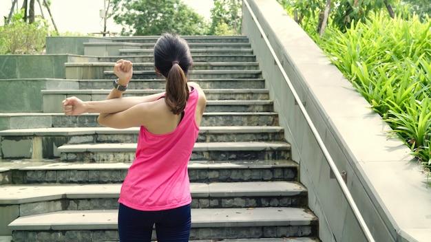 Gezonde mooie jonge aziatische atletenvrouwen in sporten die benen kleden die en haar wapens verwarmen uitrekken