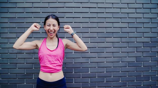 Gezonde mooie jonge aziatische runner vrouw gevoel blij lachend en op zoek naar camera na het hardlopen