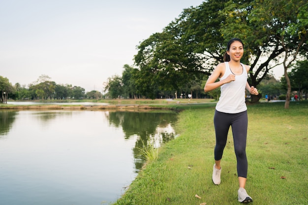 Gezonde mooie jonge aziatische runner vrouw in sportkleding lopen en joggen