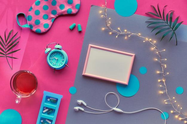 Gezonde nachtrust creatieve plat lag. frame met kopie-ruimte. slaapmasker, blauwe mint wekker, koptelefoon, oordopjes en thee. split roze en zilveren achtergrond met cirkels en palmbladeren