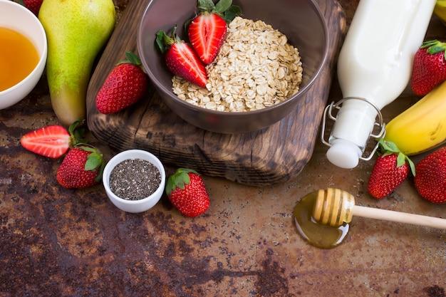 Gezonde ontbijtingrediënten: havermout, honing, fruit, aardbei en chiazaden. concept van natuurlijk biologisch voedsel
