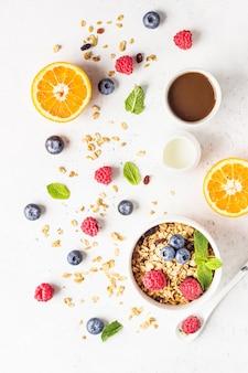 Gezonde ontbijtingrediënten: muesli met melk, bessen (bosbessen en frambozen), sinaasappel en melk.