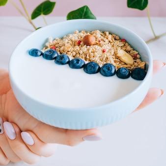 Gezonde ontbijtkom met muesli en yoghurt in vrouwenhanden op roze en marmeren achtergrond