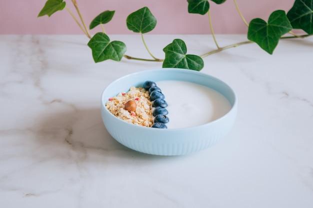 Gezonde ontbijtkom met muesli en yoghurt op roze en marmeren achtergrond.