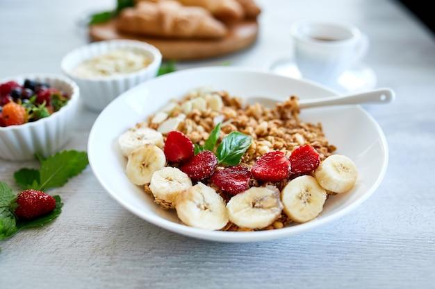Gezonde ontbijtkom, verse muesli, muesli met yoghurtvruchten en koffie, aardbei, banaan op witte lijst, exemplaarruimte. schoon eten, detox, diëten, vegetarisch voedselconcept