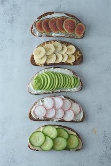 Gezonde ontbijtsandwiches met avocado, komkommer, vijgenfruit, banaan, roomkaas.