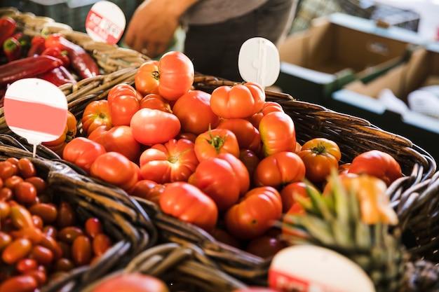 Gezonde organische groente in rieten mand met prijskaartje bij marktkraam