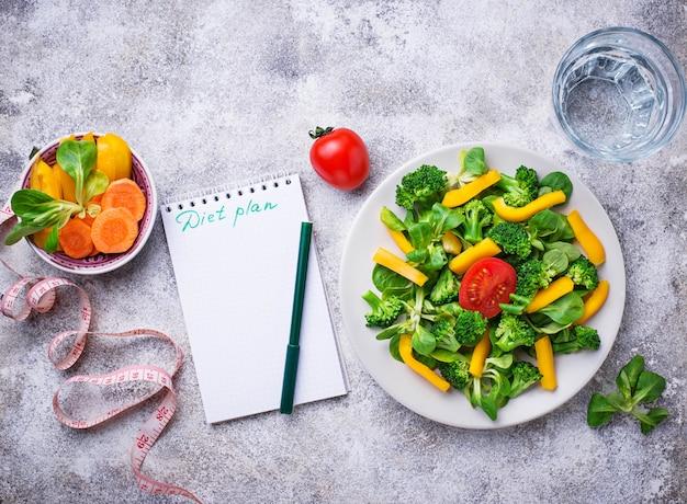 Gezonde plantaardige salade, water en meetlint