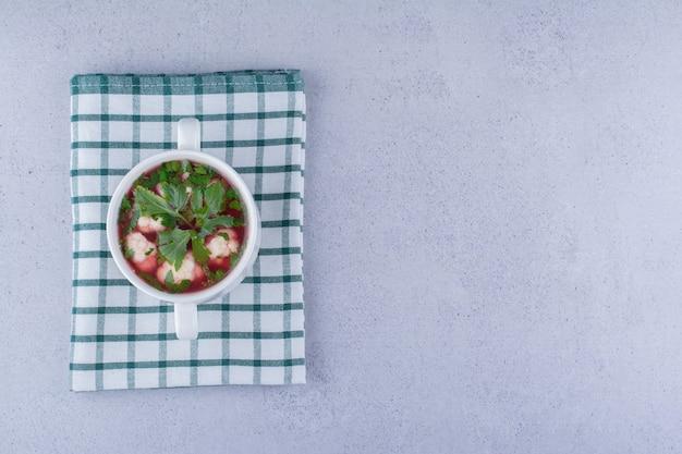Gezonde portie bloemkoolsoep in een kleine kom op gevouwen tafelkleed op marmeren achtergrond. hoge kwaliteit foto
