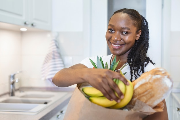 Gezonde positieve gelukkige vrouw met een papieren boodschappentas vol groenten en fruit. jonge vrouw met boodschappentas met groenten die in de keuken staat