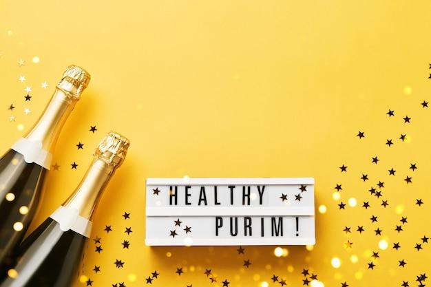 Gezonde purim geschreven in lightbox en twee champagneflessen op een gele muur. plat leggen van purim carnaval viering concept. kopieer ruimte voor tekst