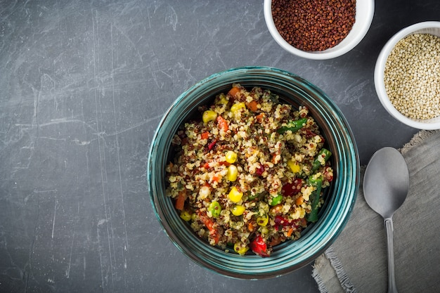 Gezonde quinoa saladeschaal en kopjes met rode en witte quinoa zaden.