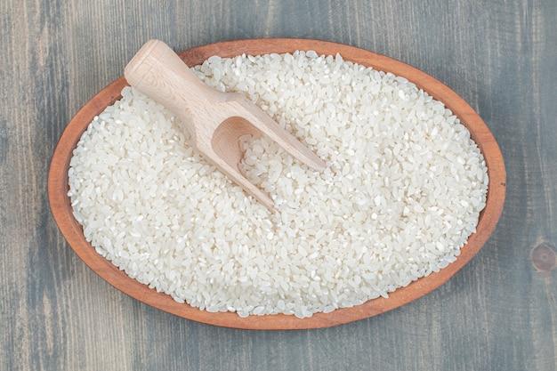Gezonde rauwe rijst met houten lepel op een houten tafel