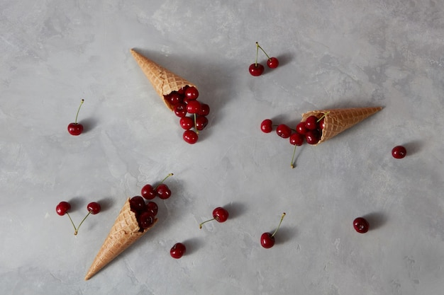 Gezonde rijpe rode vruchten kersen en wafel cups voor zelfgemaakte ijs op een grijze stenen achtergrond met plaats voor tekst. zomer biologisch eten.