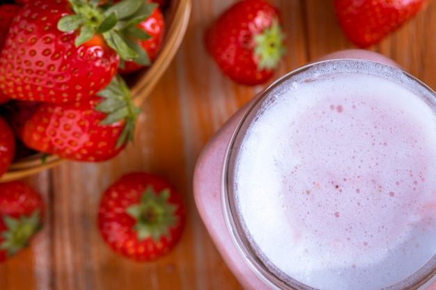 Gezonde roze smoothie met aardbei in glazen potten bovenaanzicht.