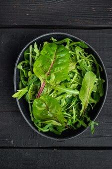 Gezonde salade, bladeren mix salade rucola, snijbiet set, op zwarte houten tafel achtergrond, bovenaanzicht plat lag