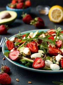 Gezonde salade met aardbeien, avocado, rucola en mozzarella, gekleed met olijfolie en balsamico dressing in een bord op een donkere