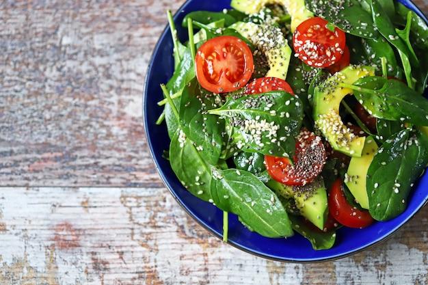 Gezonde salade met avocado, spinazie, chiazaad en sesamzaad.