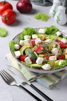 Gezonde salade met avocado, tomaten, feta en rode ui op grijze achtergrond, close-up, verticaal formaat