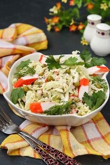Gezonde salade met chinese kool, ingeblikte erwten en krabstokken in een kom tegen een donkere lijst, close-up, verticaal formaat