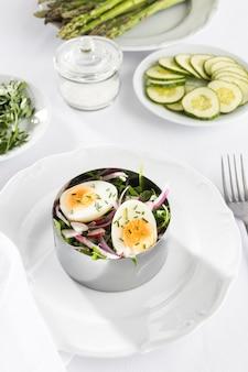 Gezonde salade met hoge hoek in het assortiment van metalen ronde vormen