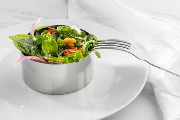 Gezonde salade met hoge hoek in ronde metalen vorm