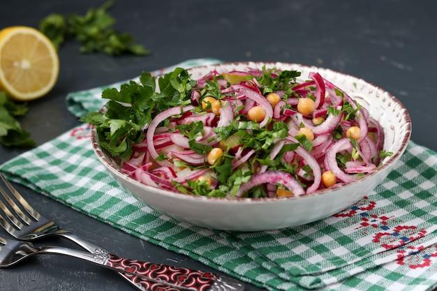 Gezonde salade met kikkererwten, aardappelen, rode uien en ingelegde komkommers in een bord