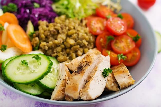 Gezonde salade met kip, tomaten, komkommer, sla, wortel, selderij, rode kool en mungboon op lichttafel.