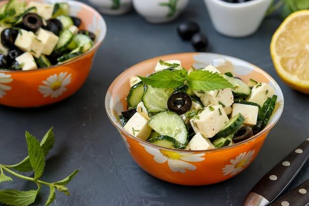 Gezonde salade met komkommers, feta en olijven, met olijfolie en groenten, gelegen in kommen tegen een donkere achtergrond, horizontale foto