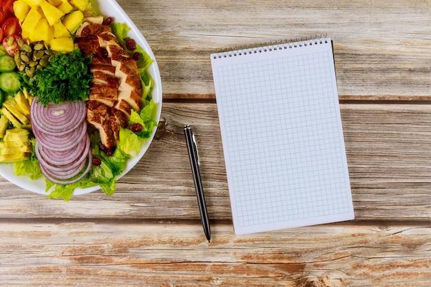 Gezonde salade met notebook en pen.