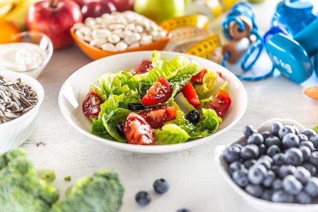 Gezonde salade met tomaten, olijven en olijfolie omringd door gezonde voeding en fitnessapparatuur