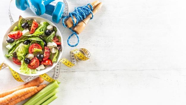 Gezonde salade met tomaten omringd met fitnessapparatuur, wortelselderij en meetlint