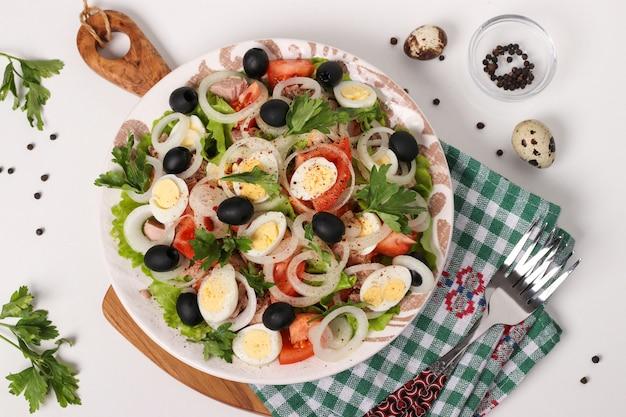 Gezonde salade met tonijn uit blik, tomaten, kwarteleitjes, zwarte olijven, witte uien