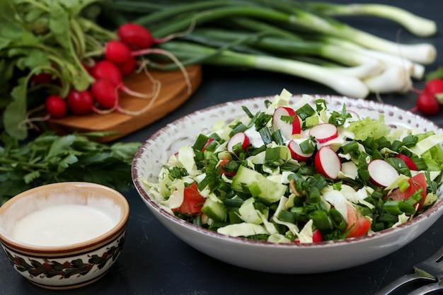 Gezonde salade met verse groenten: radijs, komkommers, groene uien, peterselie, tomaten, kool en spinazie