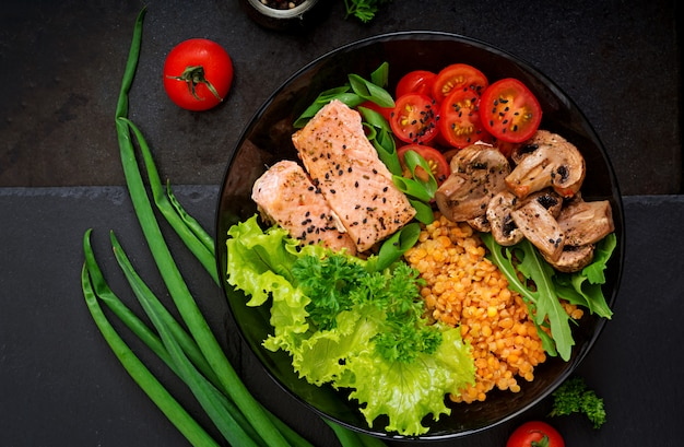 Gezonde salade met zalm, tomaten, champignons, sla en linzen op donker