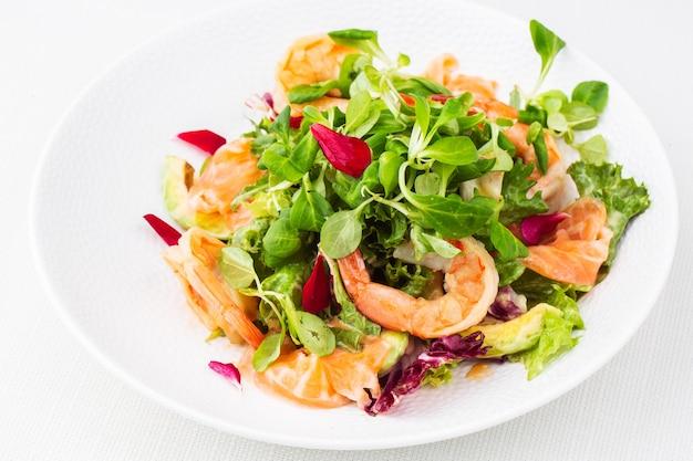Gezonde salade. recept voor verse zeevruchten. gegrilde garnalen, garnalen, verse sla en avocadoplakken.