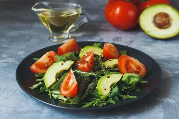 Gezonde salade tomatenmix bladeren met avocado en andere ingrediënten op een bord op grijze betonnen tafel