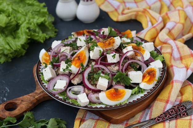 Gezonde salade van biologische sla met kip, rode biet, gekookte eieren, rode uien en fetakaas, close-up
