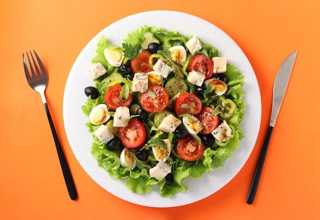 Gezonde salade van kerstomaatjes, komkommers, paprika's, zwarte olijven, met olijfolie, kwarteleitjes en gorgonzolla-kaas op een oranje achtergrond.