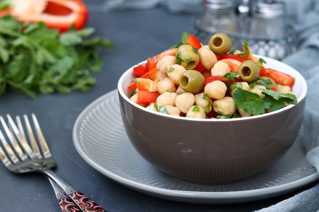 Gezonde salade van kikkererwten, groene olijven, peper en peterselie, op donker