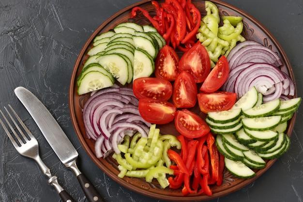 Gezonde salade van tomaat, rode ui, peper en komkommers op plaat op donker