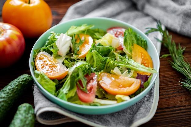 Gezonde salade van verse groenten, kruiden en tomaten op een houten ondergrond.