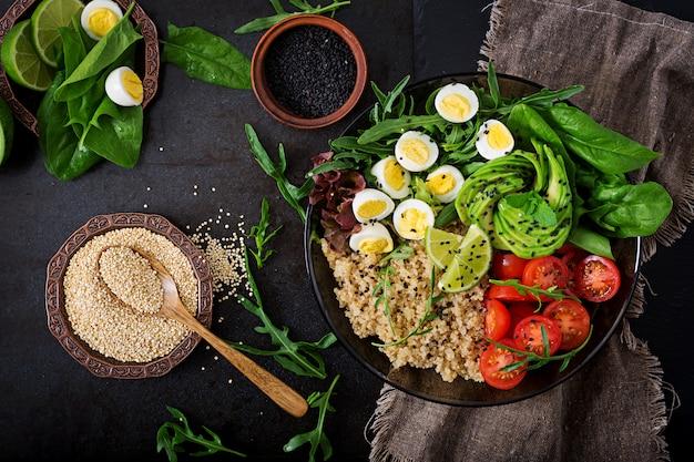 Gezonde salade van verse groenten - tomaten, avocado, rucola, ei, spinazie en quinoa op kom. plat leggen. bovenaanzicht