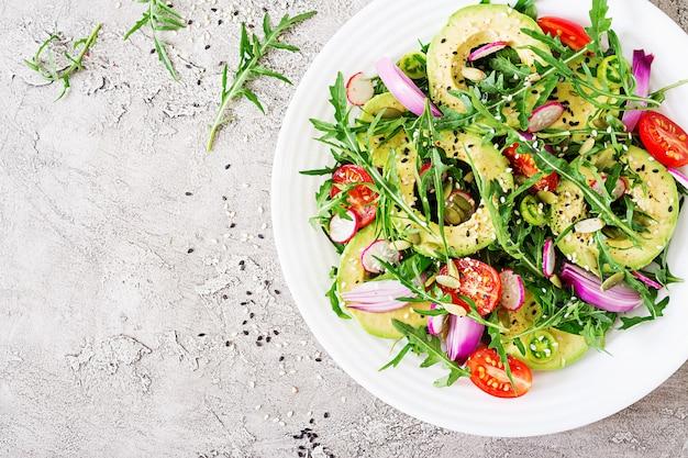 Gezonde salade van verse groenten - tomaten, avocado, rucola, radijs en zaden op een kom. veganistisch eten. plat leggen. bovenaanzicht