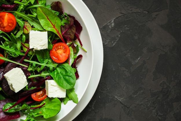 Gezonde saladebladeren in een witte plaat en een kaas (meng microgroenten). voedsel achtergrond