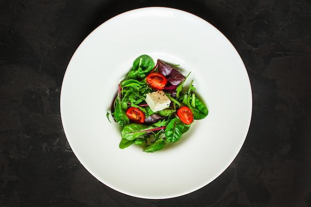 Gezonde saladebladeren in een witte plaat en een kaas (sappige snack). voedsel achtergrond