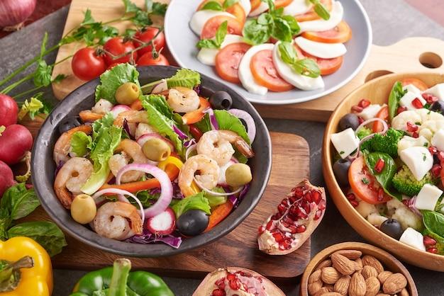 Gezonde saladeplaat. recept voor verse zeevruchten. gegrilde garnalen en verse groentesalade. gezond eten. plat leggen. bovenaanzicht. garnalensalade met tomaat, olijven en amandelnoten. meng groenten.