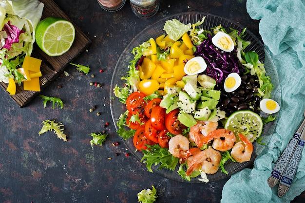 Gezonde saladeplaat. vers zeevruchtenrecept. gegrilde garnalen en verse groentesalade - avocado, tomaat, zwarte bonen, rode kool en paprika. gegrilde garnalen. gezond eten. plat leggen.